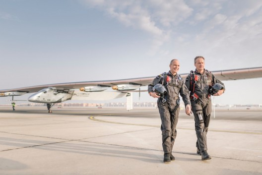 On a probably hot tarmac, Bertrand Piccard and Andre' Borschberg stand before SI2, an airplane in whch they will spend 25 days, much of those over water