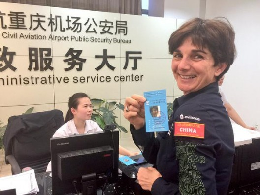 Bertrand Piccard's wife, Michelle, happily displays her pass that allows her to be on hand for SI2's landing at Chongqing.  Logistics for this trip must be daunting