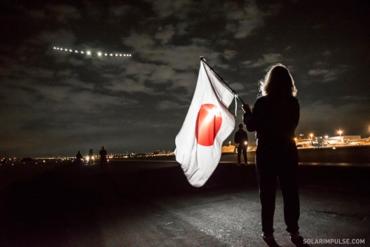 Mrs. Borschberg holds an oddly appropriate flag with Japan's rising sun sending her husband toward the dawn