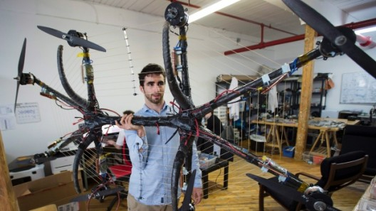Alexandru Duru holds up his hoverboard at his office in Montreal on Friday, May 22, 2015. Duru set a Guiness World Record for the longest flight on a hoverboard with a distance of 275.9 metres. (Ryan Remiorz / THE CANADIAN PRESS)