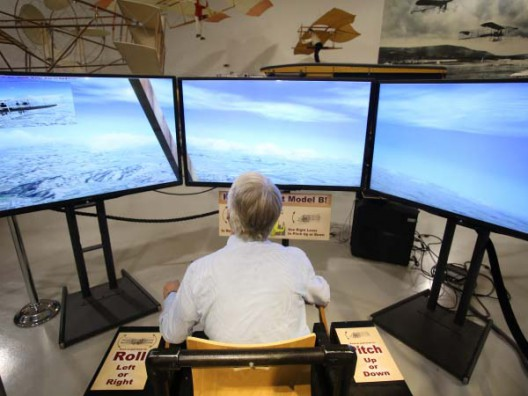 "Visitors can ""fly"" Vin Fiz on a three-screen simulator. Push and pull the left stick to go up and down, the right stick to go right and left."